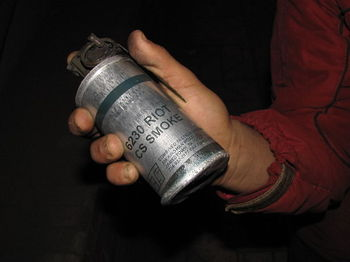 Someone holding a Tear Gas Grenade in their hand